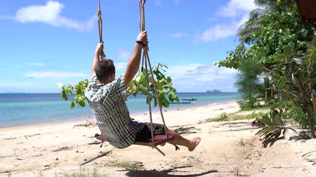 отцовство : A man swinging on a swing by the sea