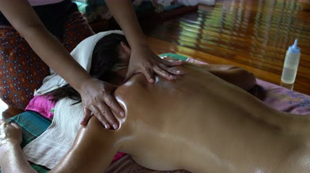 masażysta : The masseuse massages the womans back. Thai massage with oil