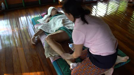soothing : The masseuse paints oil for massage on a womans foot