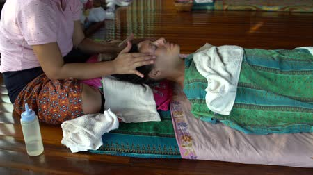 healer : Thai head massage. The masseuse massages the neck and temporal area of a woman