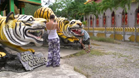 panthers : A woman is taking pictures of a man with a tiger statue.