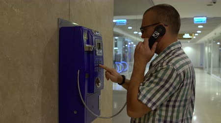 frustração : The man approaches the telephone and answers the phone and dials the number