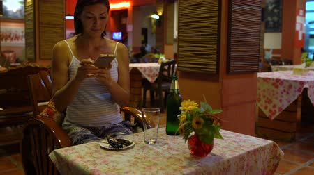 çekirge : A woman sitting in a restaurant takes pictures of fried insects on a plate. Thai food.
