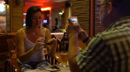 çekirge : A man takes pictures of a woman eating a roast scorpion in a Thai restaurant Stok Video