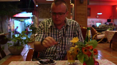 cricket : A man drinks beer and eats a roasted grasshopper in a Thai restaurant