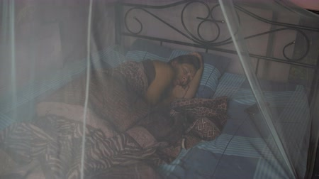 littlegirl : A woman sleeps on the bed with canopy