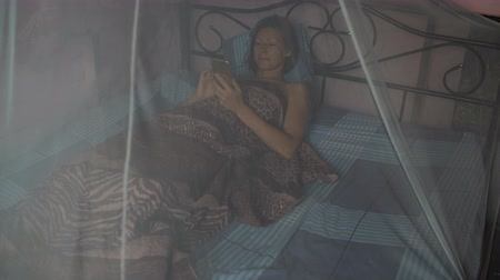 littlegirl : A woman lies in bed with a canopy and uses a smartphone