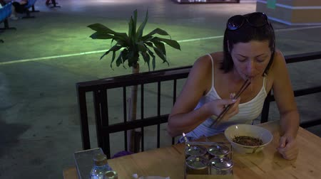 popart : Woman eating Thai noodles with vegetables and meat using sticks