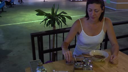 popart : A woman is sitting in a Thai cafe putting spices in food and eating Pad Thai with chopsticks