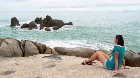меланхолия : Woman by the sea sits on the rocks