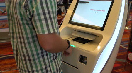 célula : Man prints a ticket at the airport terminal
