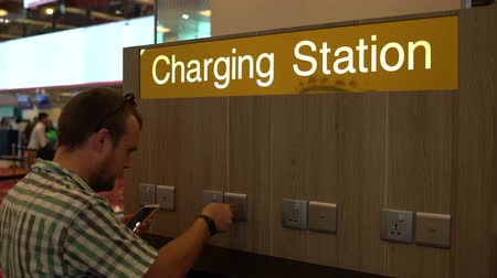 adapter : A man is charging a smartphone on the charging station at the airport Stock Footage