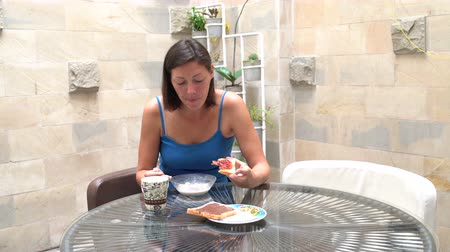 muesli : A woman is eating muesli and toast with jam Stock Footage
