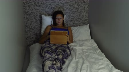 pillow block : A woman lies on a bed with an tablet PC in a capsule hotel