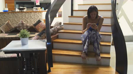 oneperson : A woman is sitting on the stairs in the house with a smartphone Stock Footage