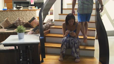 oneperson : A woman sits on the stairs in the house and uses a smartphone. A man climbs the stairs