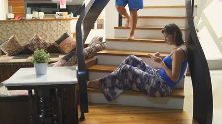 oneperson : A girl with a smartphone sits on the stairs in the house. The man goes down the stairs