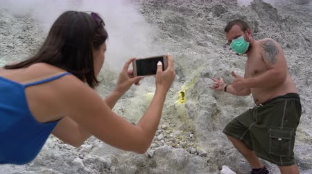 enxofre : A woman is taking pictures of a man next to a fumarole on a smartphone Stock Footage