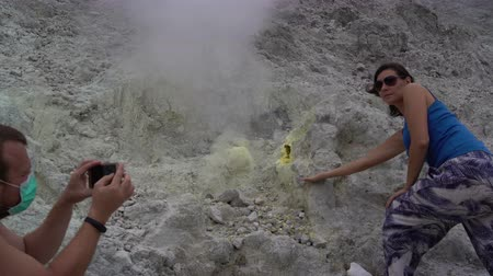 chloride : A man is taking pictures of a woman next to a fumarole on a smartphone