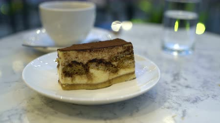 italian coffee : A female hand with a spoon breaks a piece of tiramisu in a cafe