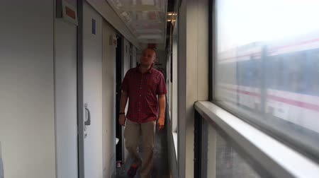 přihrádka : A man walks by the train car and enters the compartment