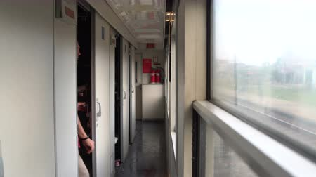 přihrádka : A man exits the train compartment and goes to the vestibule