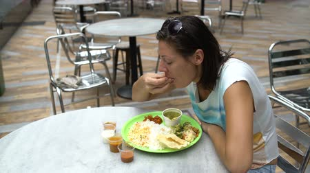 south asian food : Street Indian food Thali. A woman is eating rice with her hands