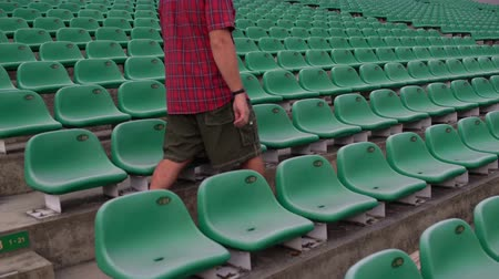 lugares sentados : A man at the stadium sits in a chair in the viewing sector