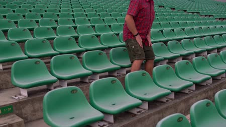 bleachers : A man sits down in an armchair in an empty stadium Stock Footage