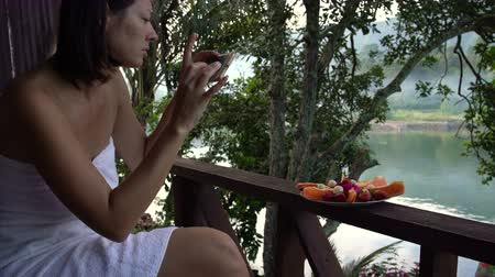 banan : A woman in a towel takes pictures of a plate of fruit against the lake