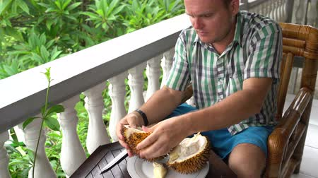 mal cheiroso : A man cleans durian with his hands