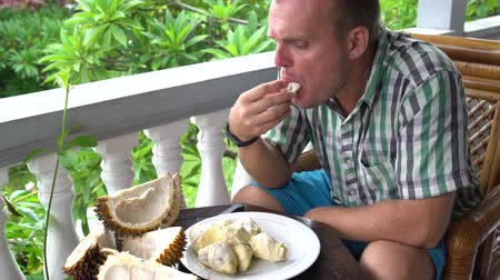 saborear : A man sitting on the balcony eating durian