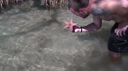 starfish : The man lifts the starfish from the bottom