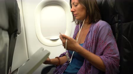 comfortable seat : A woman sits on a plane, uses a smartphone and lowers a folding table Stock Footage