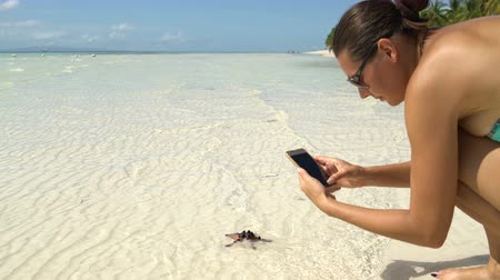 lifebuoy : A woman in a swimsuit takes pictures of a starfish on a smartphone