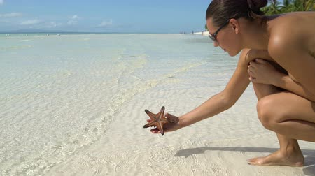 concha : A woman in a bathing suit takes a starfish and puts it back