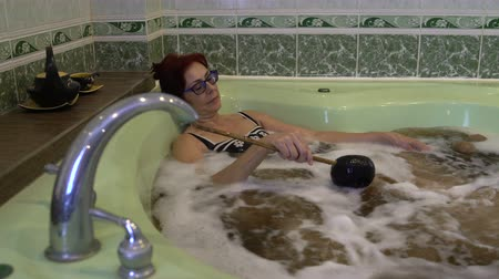 banheira : A woman lies in a bath with mineral water and herbs and pours itself out of the bucket