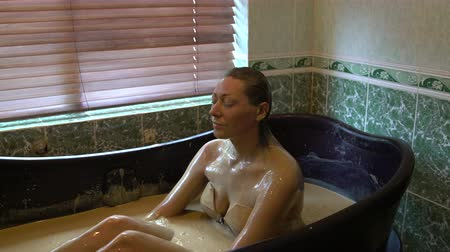 bahno : The girl sitting in the bath with healing mud and washes her face Dostupné videozáznamy