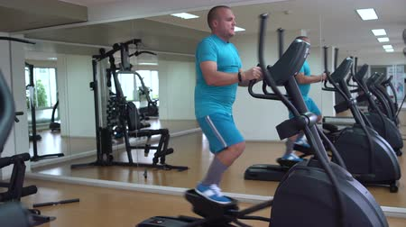 spotswear : In the gym, the man has an elliptical exerciser