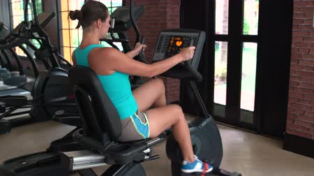 exercisemachine : A woman has on a stationary bike