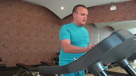 bieżnia : A man walks on a treadmill at the gym