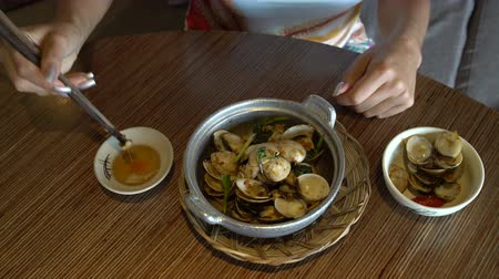 лапша : The female hand takes the mussel from the shell with chopsticks and dips it into the sauce Стоковые видеозаписи
