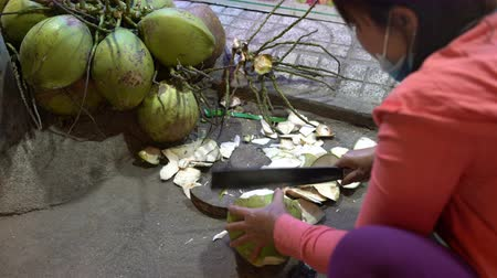 machete : A woman cleans a young green coconut with a knife Stock Footage