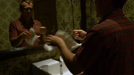 lavatório : A man washes his hands in a sink and wipes himself with a towel