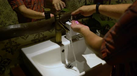 sanitize : A man washes hands with soap in a sink Stock Footage