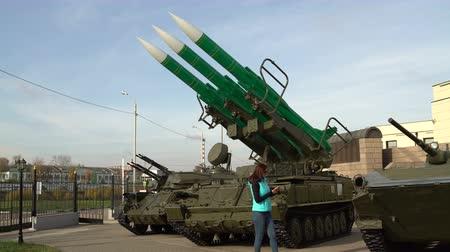 Girl takes foto on the smartphone self-propelled launch system of the anti-aircraft missile system