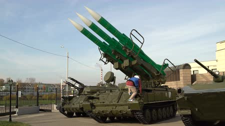 anti war : A woman photographs a man standing on a self-propelled launcher anti-aircraft missile system. Stock Footage