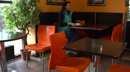 A woman in a cafe with a tray sits at the table and eats 影像素材