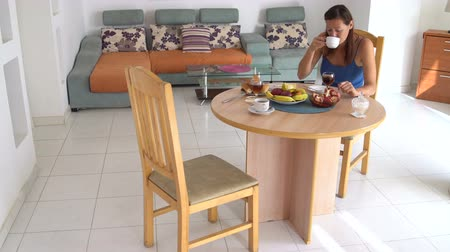 Woman sitting at a table having breakfast at home