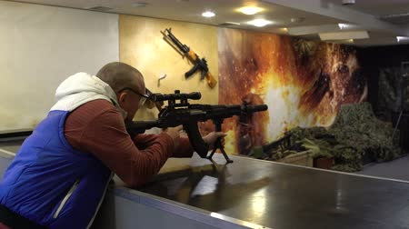 Shooting range. A man in glasses aims and shoots from a Kalashnikov assault rifle at metal targets.